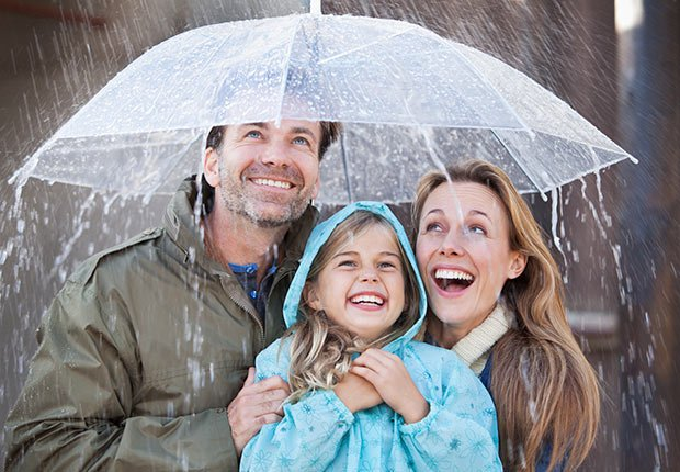 Enthusiastic family under protected under umbrella in a downpour. 10 Things You Need to Know About the Health Care Law