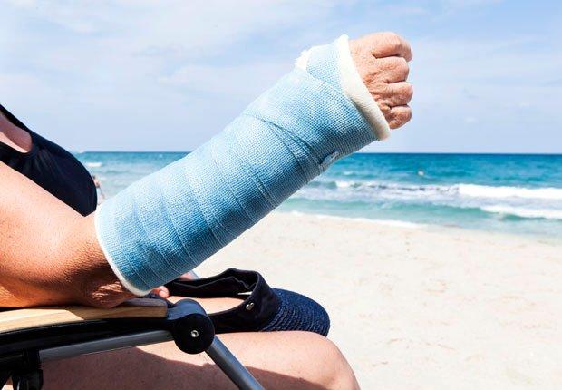 Mujer sentada en la playa con un brazo enyesado - Consejos para verse y sentirse bien este verano