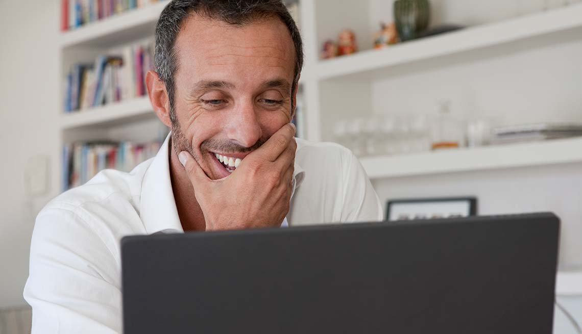 Man laughs at something on laptop, Reduce Stress with humor