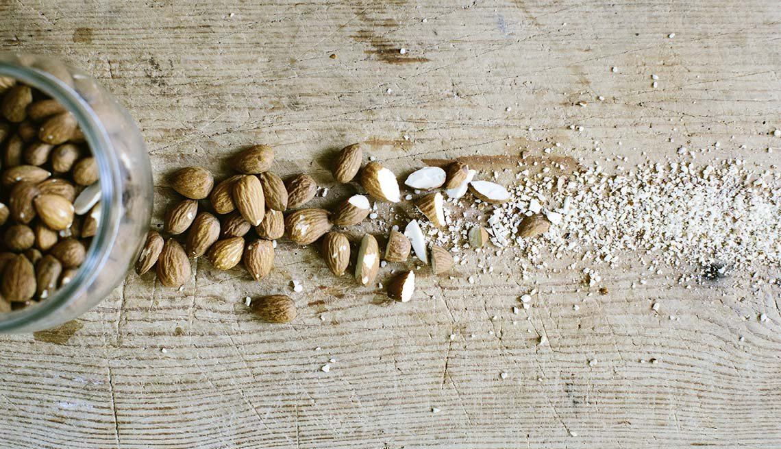 Whole and chopped almonds on a board, Nuts for Health