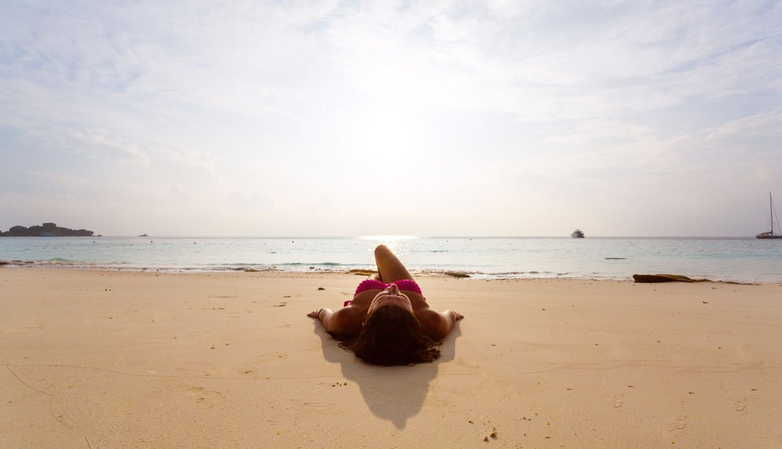 Woman lying on a beach, Stay Healthy on Vacation