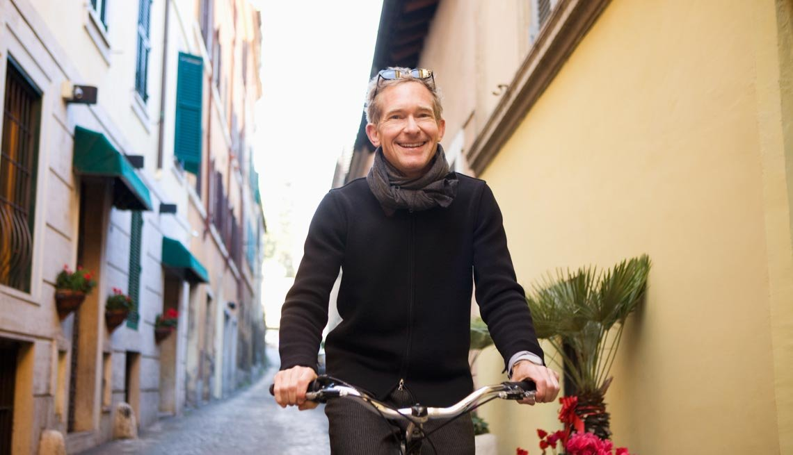 A man bikes on a narrow pavement, Stay Healthy on Vacation