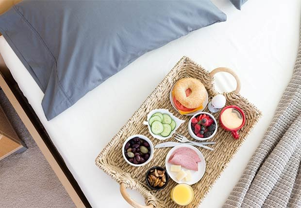 Breakfast Tray on Unmade Bed in Hotel Room, 6 Ways to Stay Healthy on Vacation
