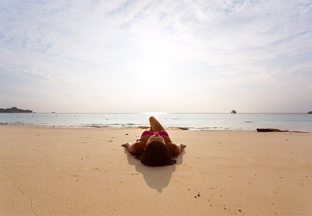 Woman sunbathing on the beach, 6 Ways to Stay Healthy on Vacation