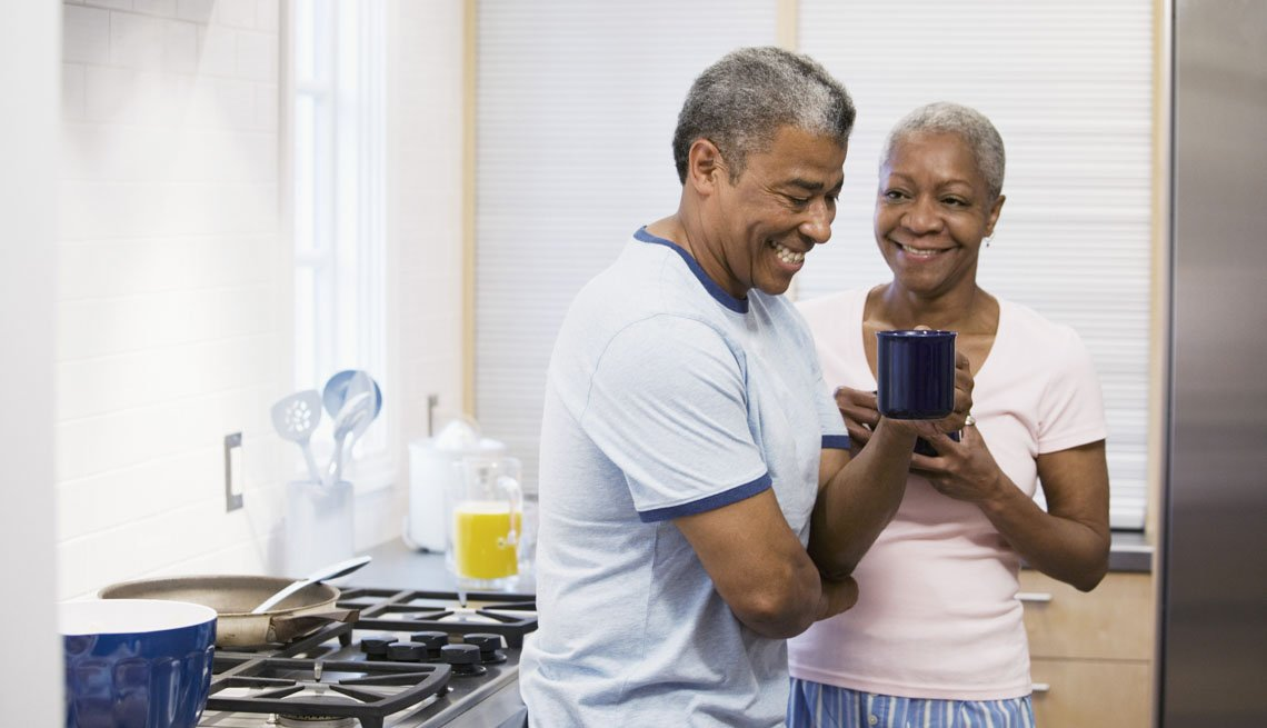 Husband and wife while laughing while drink coffee, 7 Ways to Make Your Morning Healthier