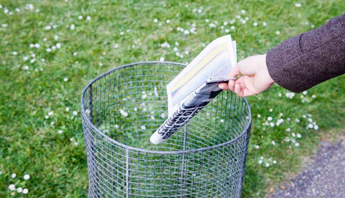 Hand throwing morning newspaper in trash can, 7 Ways to Make Your Morning Healthier