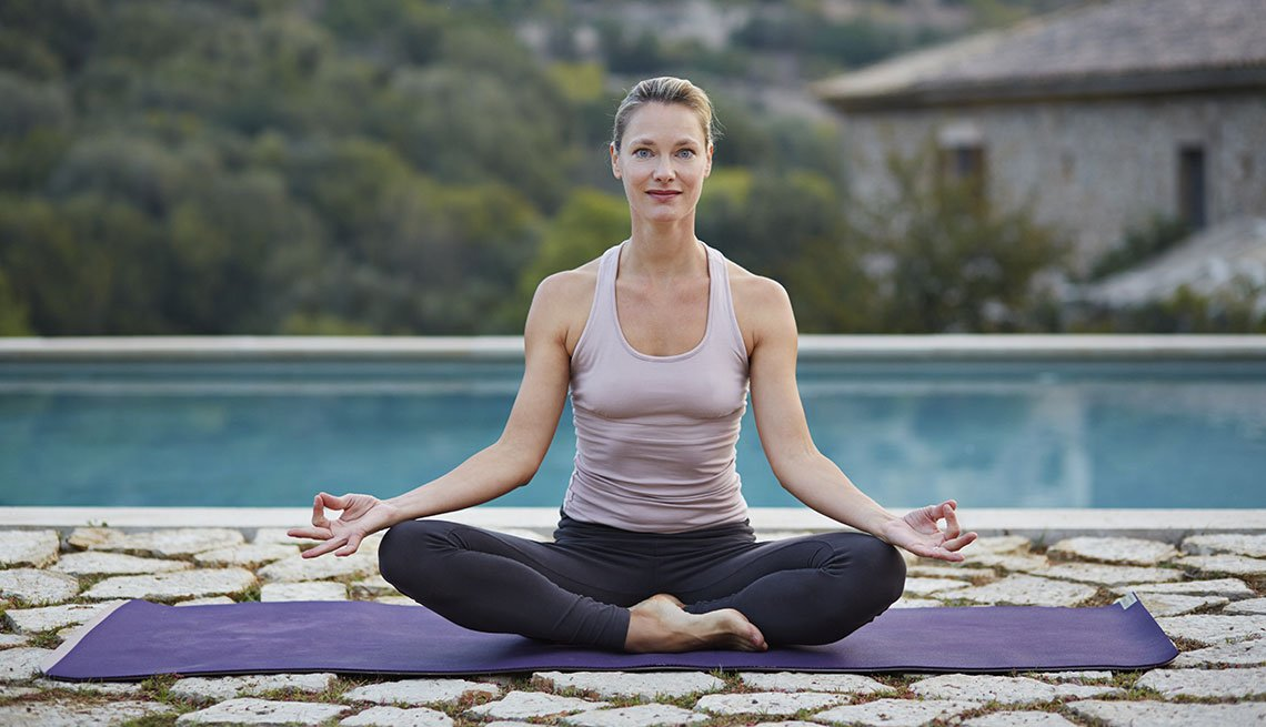 Mature woman exercising Yoga outdoors
