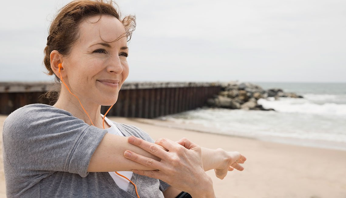 Smiling woman stretching arm on beach