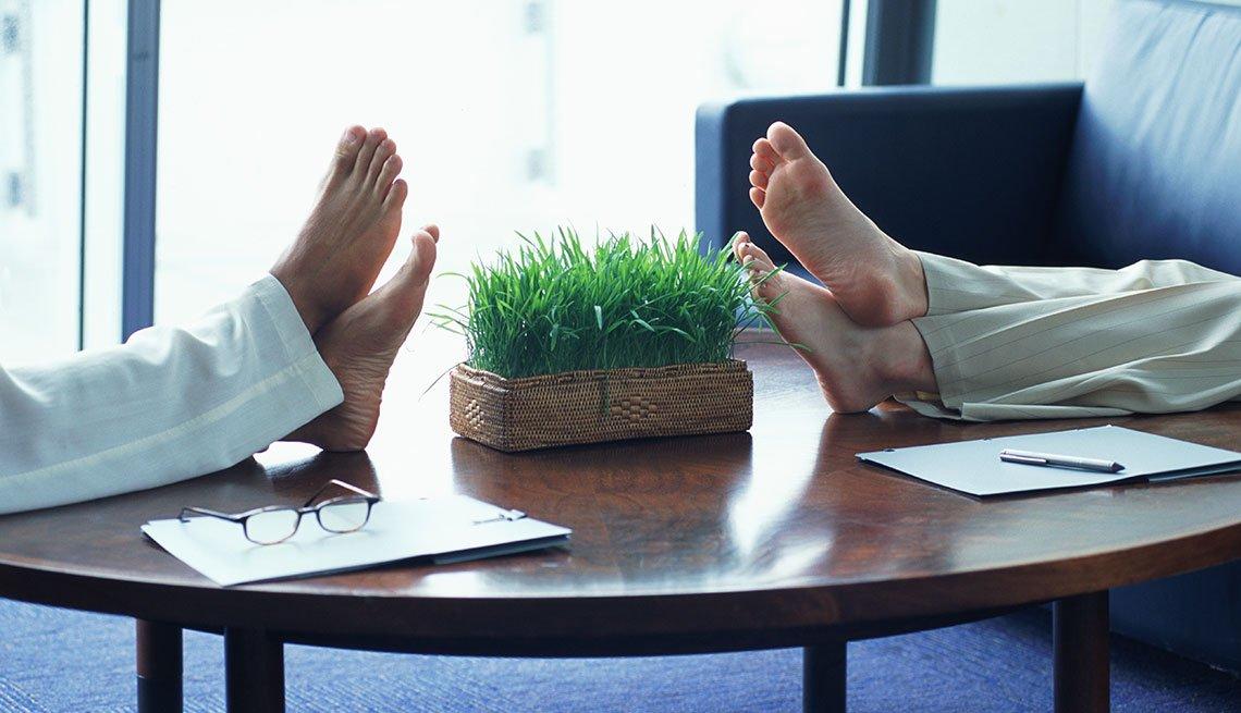 Personas con sus pies sobre una mesa