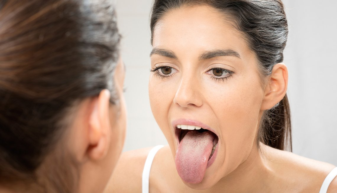 Woman looks at her tongue in a mirror, Health Boosters