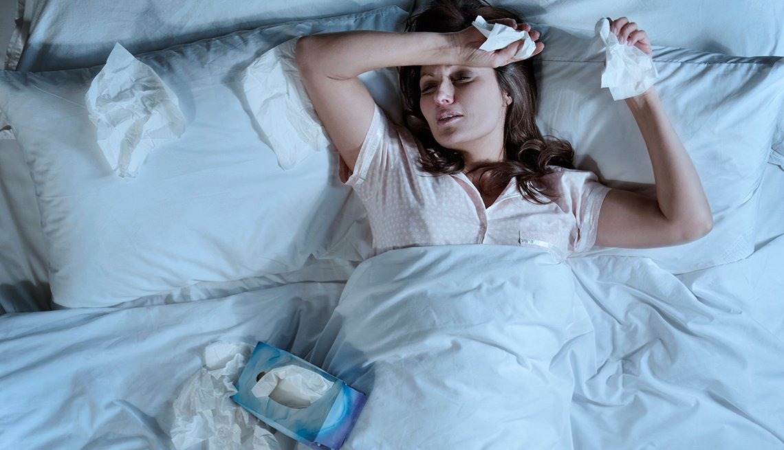 Woman in bed with flu, tissues, Health Numbers You Need to Know