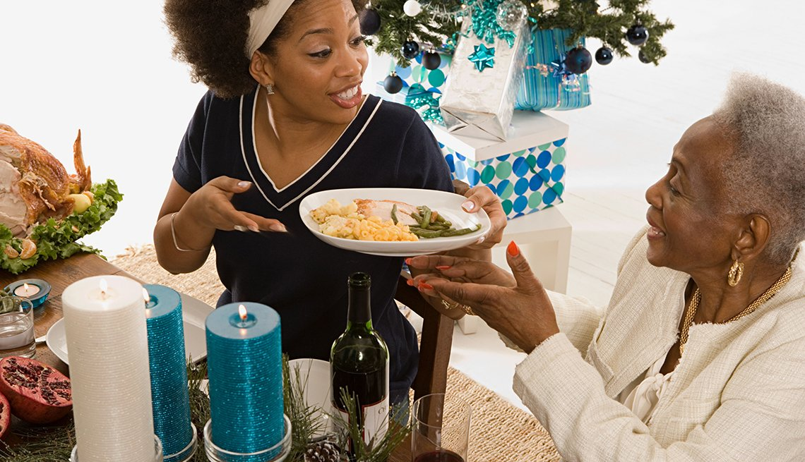Woman offers plate of food, holiday table, How Not to Gain Those 10 Holiday Pounds