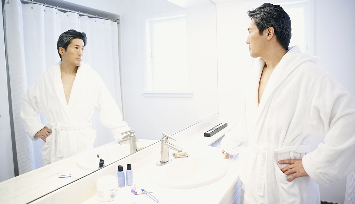 Man in robe looks in a bathroom mirror, 7 Reasons to Have More Sex After 50