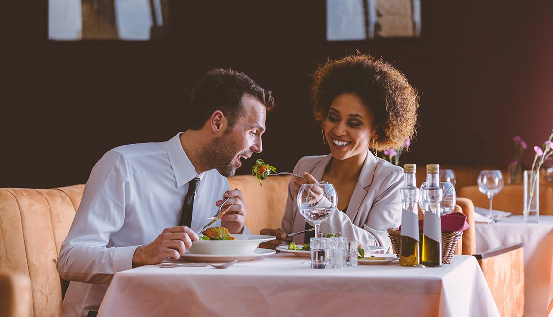 couple feeding food to each other at a restaurant on a date