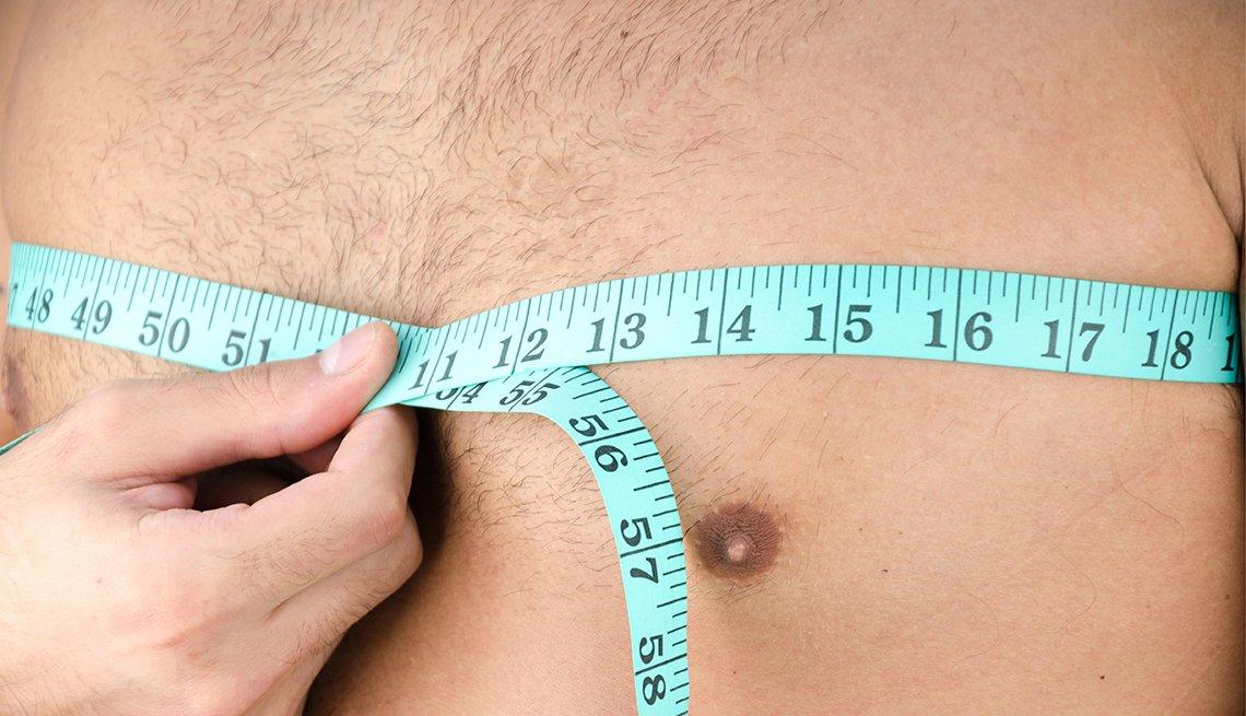 Persona midiendo el pecho de un hombre - Ginecomastía