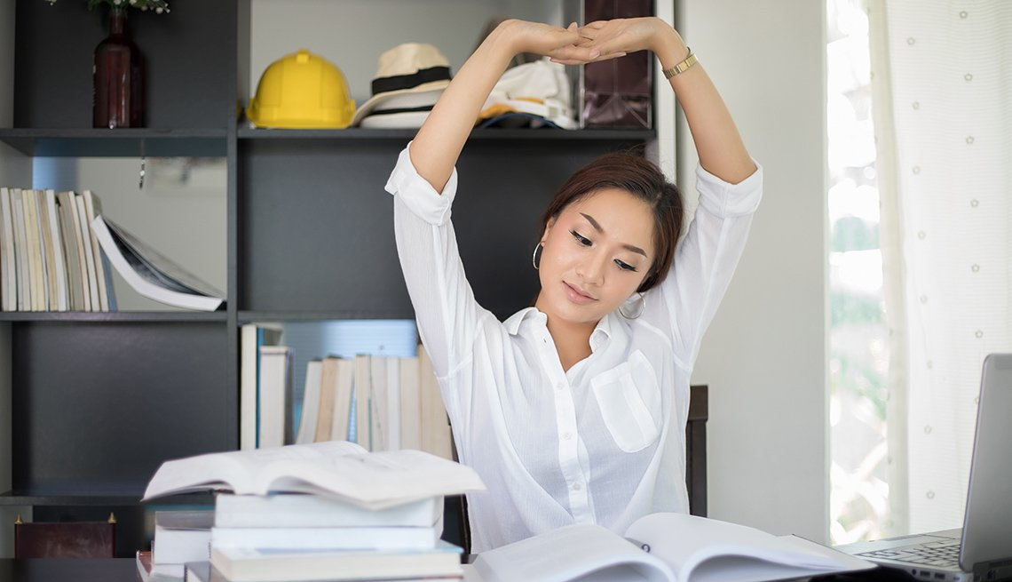 Asian Woman Sitting At Her Office Desk And Stretching, Healthy Tips While Sitting At Your Desk