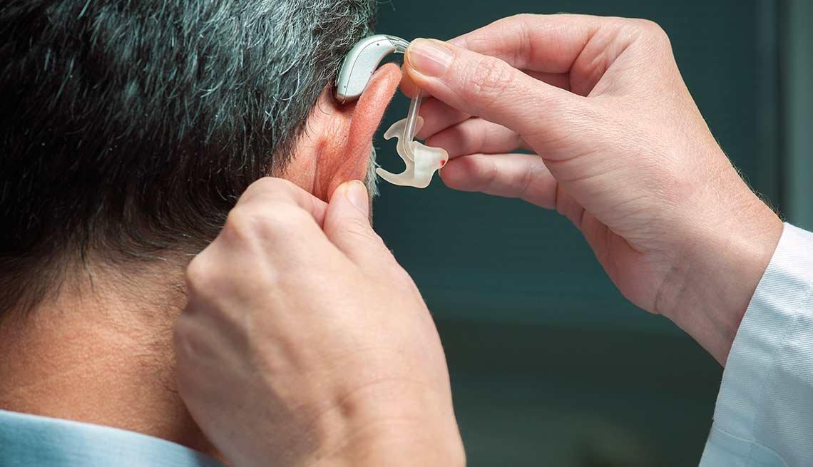 Médico colocando audífono a un paciente
