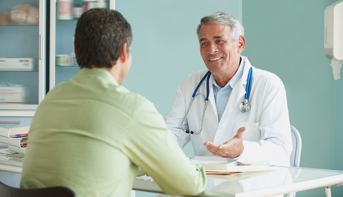 Doctor Speaking To Patient In Office, Living With Medicare