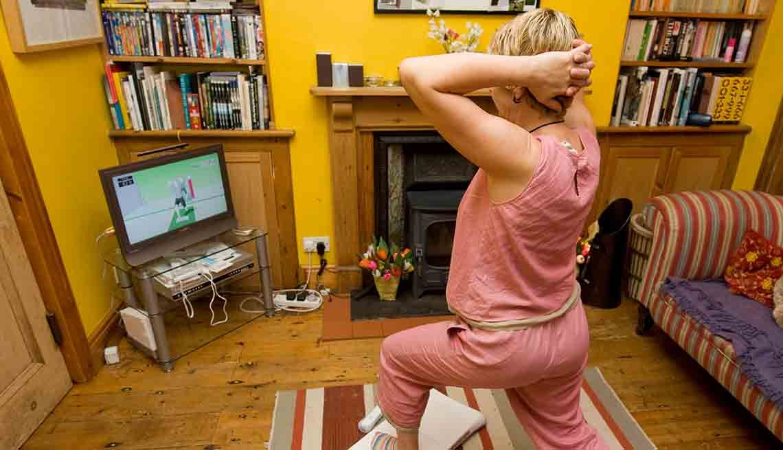 Mature woman doing yoga exercises on a Nintendo Wii Fit in the living room of her house, How Caregivers Can Find Time to Exercise