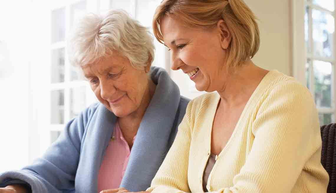 Senior mother and daughter reading together, Ask the Caregiving Resource Center Expert