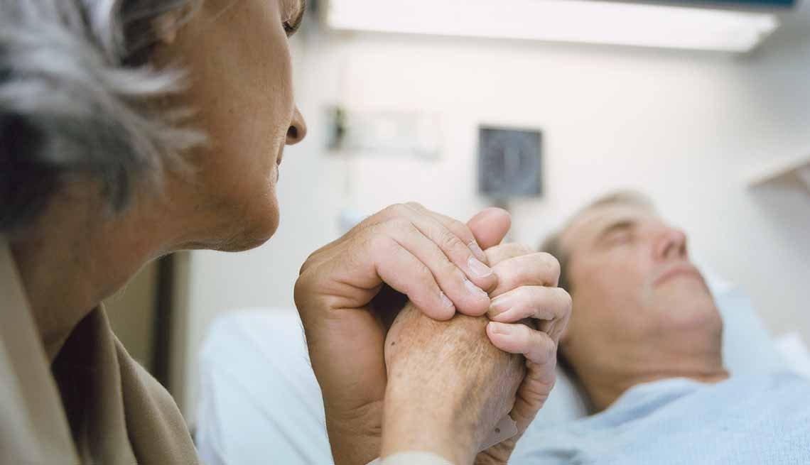 Mujer sostiene la mano de un hombre que está en el hospital - La alimentación artificial al final de la vida