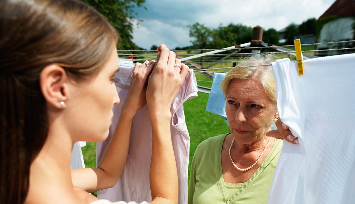 Woman Hanging Clothes Outside, Older Woman Watching, Caregiving