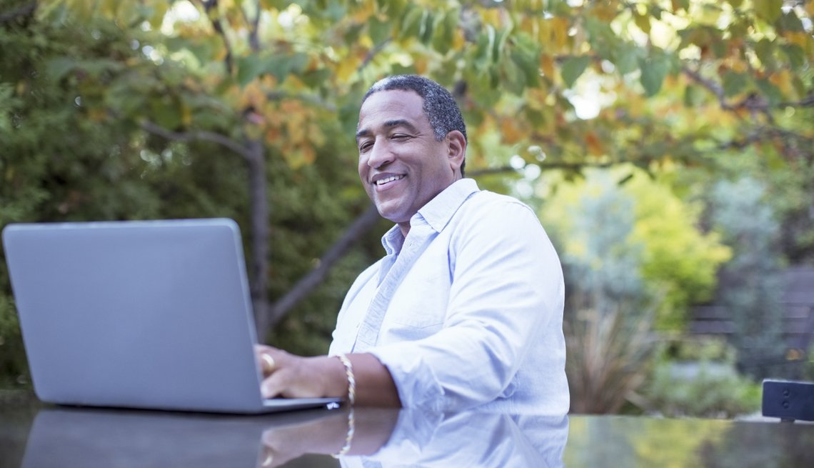 Senior man using laptop at patio table, Online Dating Not Working for You?