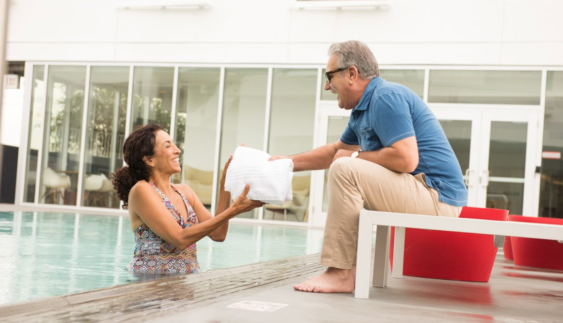 Senior man handing towel to a woman from poolside, Where To Meet Great Singles