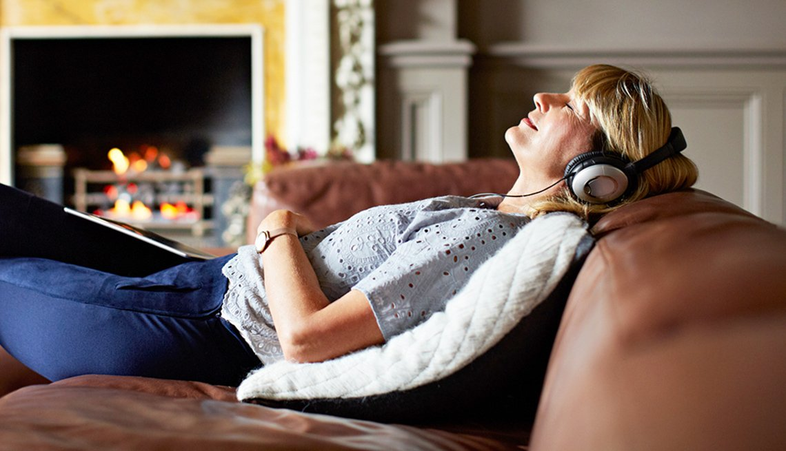 Mature woman listening to music with headphones
