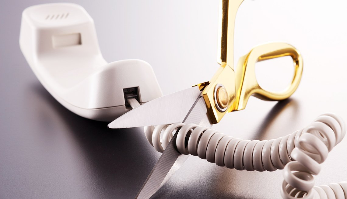 Scissors cut the cord of a wired phone