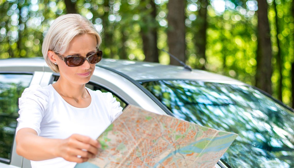 Woman in sunglasses looking at road map next to her car