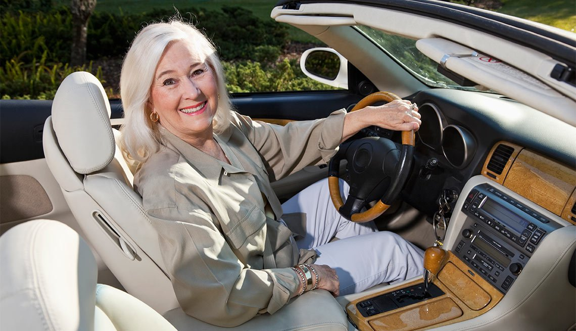 Happy woman with hand on steering wheel in convertible