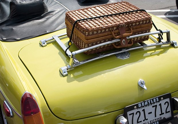 Lime green collectors MG convertible with wicker suitcase strapped to trunk, 6 things you need to know about buying and owning a convertible