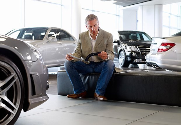 Man looking at brochure in automobile showroom, 6 things you need to know about buying and owning a convertible