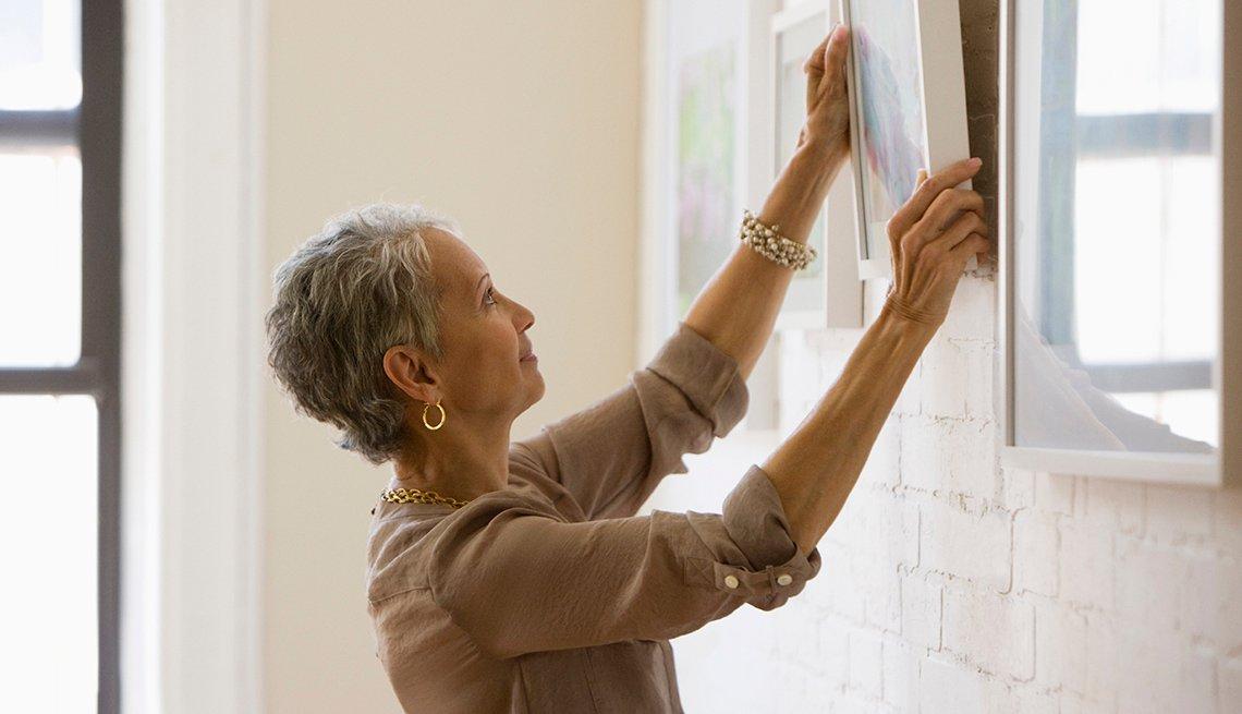 Mujer colgar cuadros en la pared, Mezcla lo antiguo con lo nuevo