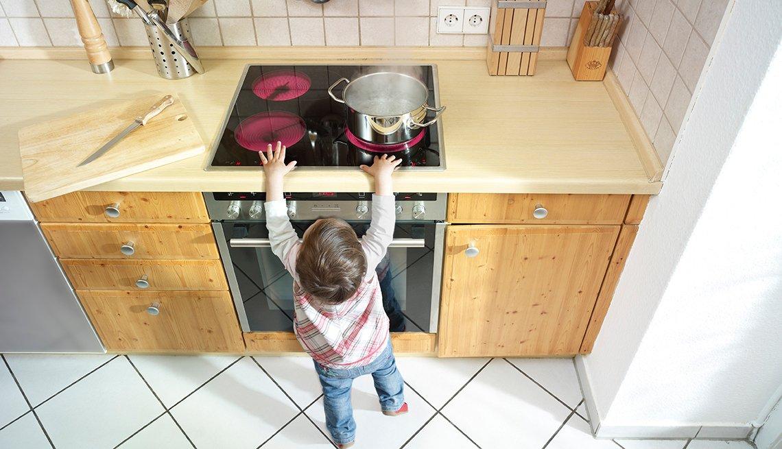 El pequeño niño se coloca cerca de una estufa, 10 consejos para prevenir accidentes en el hogar.