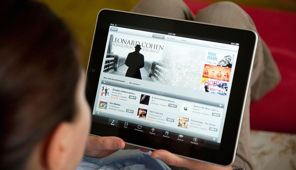 Persona mirando hacia una tableta electrónica - Sitios web y apps para hacer tus compras de fin de año