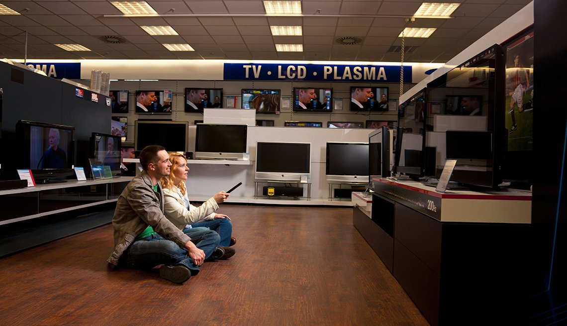Two mature adults watching TV at an electronics store