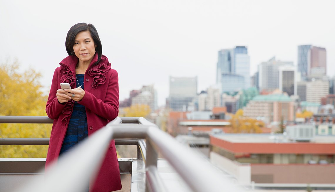 Middle-aged Asian woman using cell phone on rooftop patio.