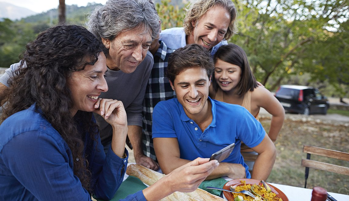 Multigenerational family looking at video on phone