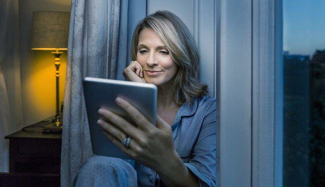 Woman using tablet at night