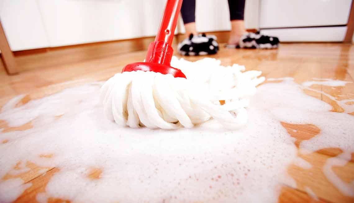 Errores que cometemos al limpiar y cómo evitarlos - Persona limpia piso de madera