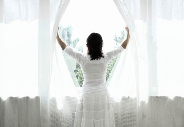 Mujer abriendo las cortinas de su casa - 10 ideas para arreglar su casa