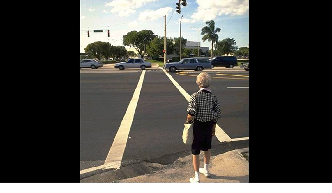 An older woman attempts to cross a very wide roadway.