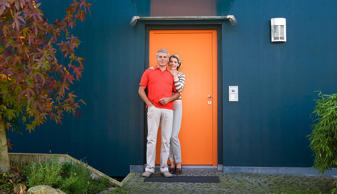 Mature Couple Stands Outside Of Their Home, Livable Communities, 8 Features Of An Age Friendly Community