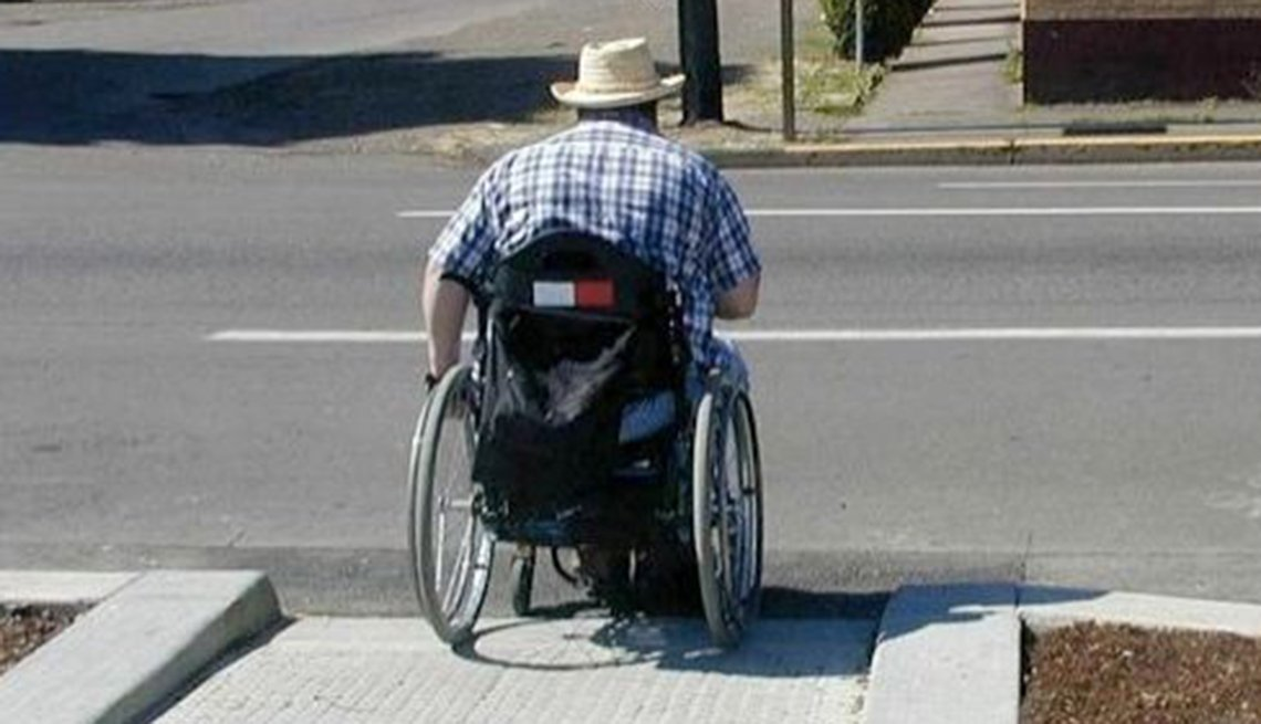 A man in a wheelchair uses a ramp on one side of a street and then sees that there's no ramp on the other side.
