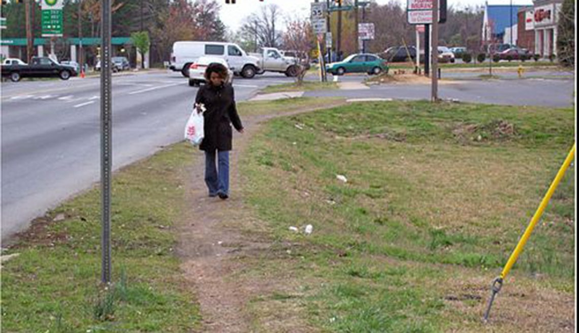 A woman returns from a store by walking along a worn down path in the grass.