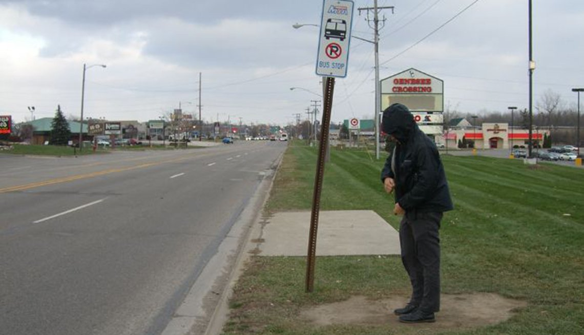 A man stands at a chilly bus stop that provides no seating or shelter.