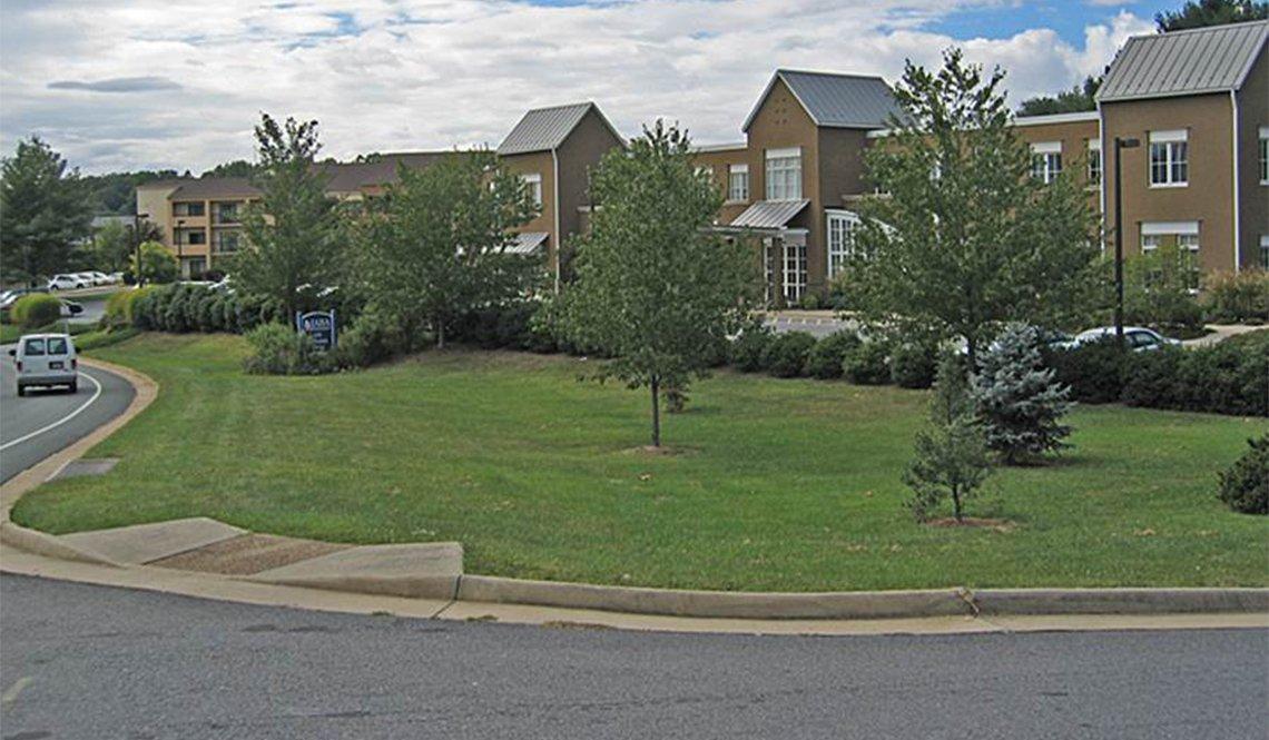 A sidewalk ramp leads to a lawn rather than a sidewalk.