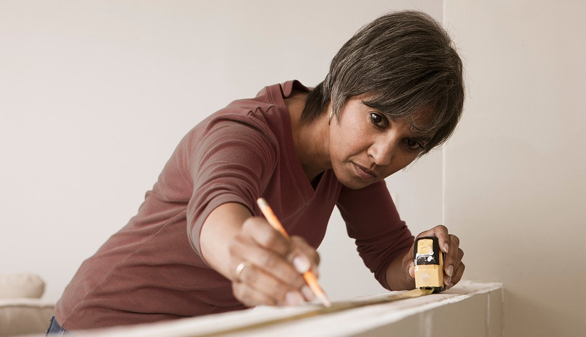 African American Woman Using Measuring Tape And Marking With Pencil, Home, AARP Livable Communities, Home Remodeling Before And After
